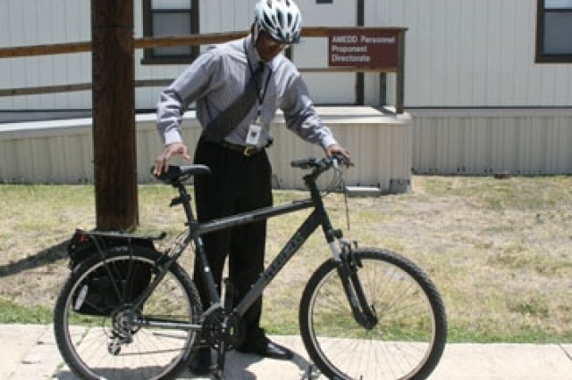 "Carlton Bray, antiterrorism specialist, Directorate of Plans, Training, Mobilization and Security, prepares to ride one of the new ""Go Green"" mountain bikes wearing a safety helmet to his afternoon meeting May 30 on Fort Sam Houston."