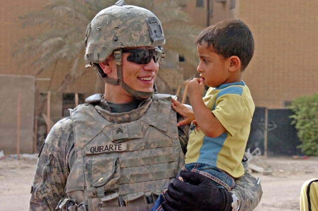 Sgt. Joseph Quirarte, a non-commissioned officer from Pacifica, Calif., takes a moment to hold an Iraqi child while on patrol in a neighborhood near the forward operating base, May 31. Quirarte serves with Military Police Platoon, Brigade Special Troop Battalion, 4th Brigade Combat Team, 10th Mountain Division (Light), Multi-National Division-Baghdad.