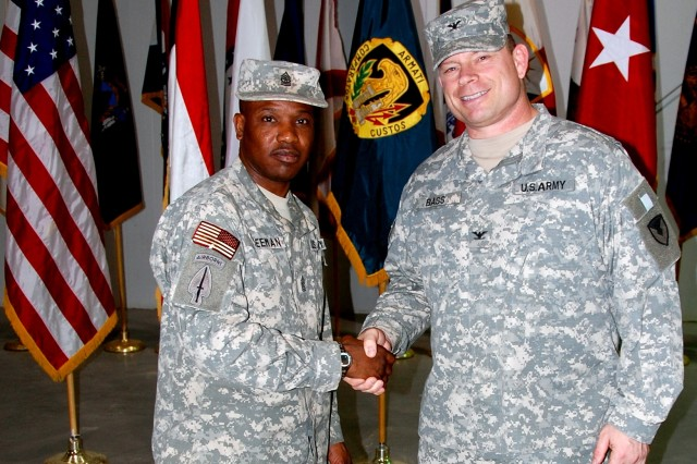 Colonel Joseph L. Bass, former commander, 408th Contracting Support Brigade, accepts a brigade coin from Sgt. Maj. Michael J. Freeman following the brigade change of command ceremony, June 6, 2008, at Camp Arifjan, Kuwait.