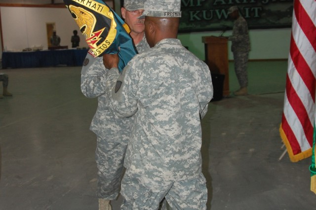 Colonel Shane Dietrich, commander, 408th Contracting Support Brigade passes the Expeditionary Contracting Command colors to Sgt. Maj. Michael J. Freeman during a ceremony, June 6, 2008, at Camp Arifjan, Kuwait.