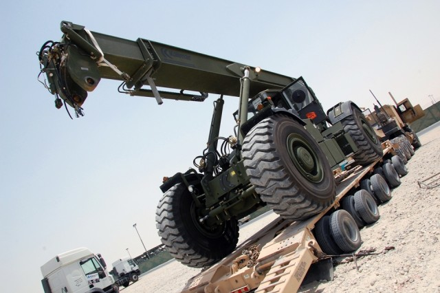 A new RT 240 'Kalmar' Rough Terrain Container Handler, bound for use in Operation Iraqi Freedom, is guided into position on an M1000 Heavy Equipment Transport Semitrailer, Monday, June 3, 2008 at Camp Arifjan, Kuwait.