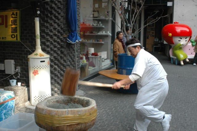 A man in traditional labour dress hammers down ddukmae, which is the old fashioned way to make rice cake. Many food stalls display a visual presentation of how food is prepared in Insadong.