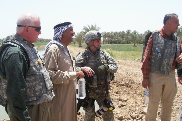 Lieutenant Colonel Bruce Baker, economics officer for MND-C, talks with George Stickles (far left), agriculture adviser for North Babil embedded Provincial Reconstruction Team, the local sheikh for an area fish holding pond and his interpreter. Team Borlaug's expertise will be implemented to put this and similar projects into action.