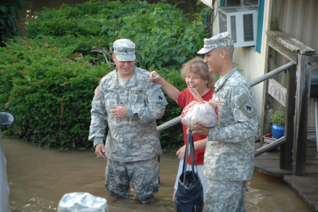 Brenda Cramer, a resident of Martinsville, Ind.,  receives help evacuating her flooded home from Spc. Tony Pierle and Sgt. Brian Huckins, 1st Battalion, 150th Field Artillery. She was helped into a rescue vehicle that took her to higher ground Saturday. Residents were forced out of their homes by flash floods that raged through the area.