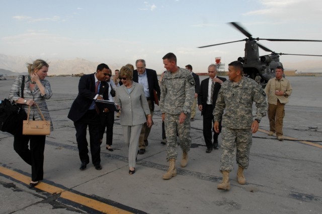 First Lady Laura Bush is greeted by Maj. Gen. Jeffrey Schloesser, the Combined Joint Task Force-101 commanding general, and Command Sgt. Maj. Vincent Camacho, the CJTF-101 command sergeant major, just after landing at Bagram Air Field on June 8, 2008.