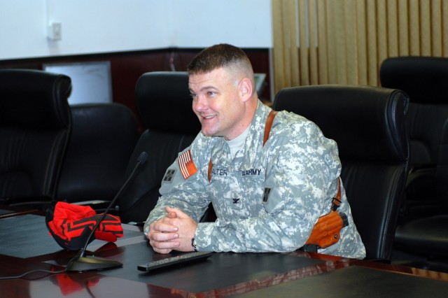 Col. Bill Salter, the Baghdad Operations Command Advisory Team Chief, using video teleconference technology during the Iraq early morning of June 8, spends some time with his Family prior to his son William's graduation from Harker Heights High School. The teleconference was held from the MND-B staff conference room, at the MND-B headquarters building and the Bell County Expo Center in Belton, Texas. William is preparing to enter the United States Military Academy at West Point in the fall.