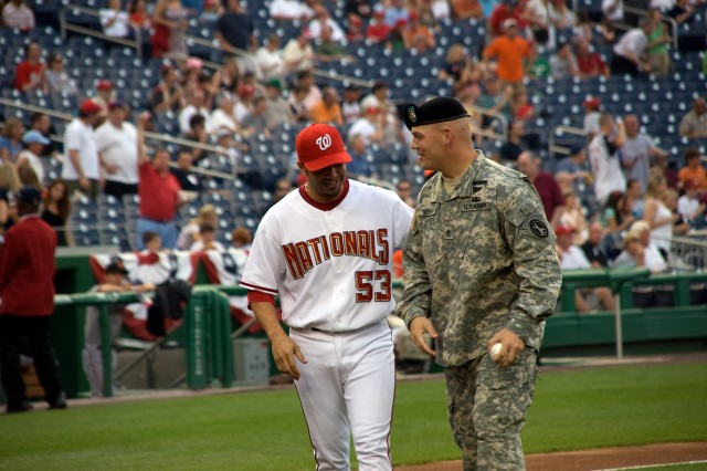 "Staff Sgt. Jason Seifert, 4th Squad Leader, 1st Platoon, A Co., the Old Guard, Fort Myer, Va., meets with Washington Nationals catcher Wil Nieves prior to the start of a June 6 game between the Washington Nationals and the San Francisco Giants at Nationals Park, Washington, D.C. Seifert was named Army NCO of the Year and was given the opportunity to throw out ""the first pitch"" prior to the start of the game. The evening was billed as ""Army Night"" at the stadium."