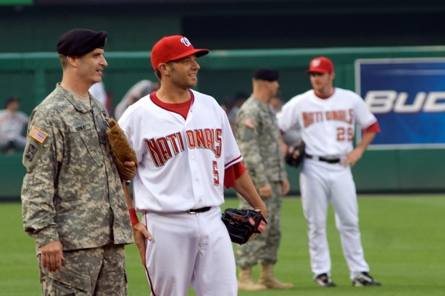 """Maj. Jeff Burke, 202nd Military Intelligence Squadron, D.C. National Guard talks with Nationals left fielder Kory Casto, before a June 6 game between the Washington Nationals and the San Francisco Giants, at Nationals Park, Washington, D.C. The evening was billed as """"Army Night"""" at the stadium."""