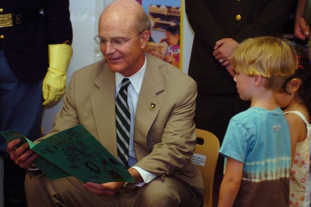 """Secretary of the Army Pete Geren enjoys an Army birthday card presented by young Army family members at the Fort Myer Child Development Center, June 9. The Secretary kicked off the 233rd Army Birthday Week celebration by reading the """"Happy Birthday Army"""" storybook to children at the CDC and sharing a birthday cake."""