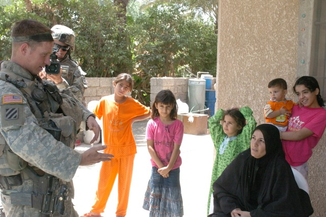 Maha Aziz Abass al-Jabouri, Alemia Rasheed Women's Council representative for Alemia, speaks with 1st Lt. Charles Staab, 2nd Brigade Combat Team, 3rd Infantry Division, June 5 outside her home.