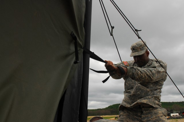 Army Sgt. Michael Brown, 237th Personnel Services Battalion, Ohio Army National Guard, helps to secure a tent against strong winds during a quartering party,  June 9, at Camp Grayling, Mich. More than 2,200 Ohio troops converged on the Michigan training site in the past week to conduct their annual training exercise.