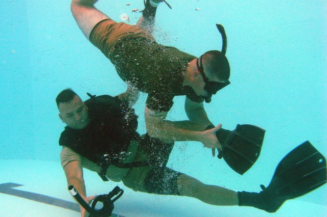 "Experienced salvage diver Sgt. Lance Little (top) ""attacks"" Sgt. Roel Ramos during repeated pool ""hits"" by taking off his mask and removing his swimming fins. Prospective dive school students must overcome panic and perform corrective actions with one precious breath of air."
