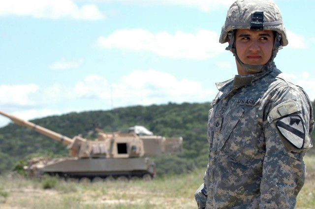 Pfc. Jose A. Hercules, a field artillery crewman from Miami, Fla. with Battery B, 2nd Battalion, 82nd Field Artillery Regiment, 3rd Brigade Combat Team, 1st Cavalry Division, observes from a distance as shots are fired from an M109A6 Paladin at Fort Hood, Texas, June 3. Hercules was operating the Paladin while members of a videography crew from The Military Channel filmed the cannons as part of a series scheduled to be released early next year.