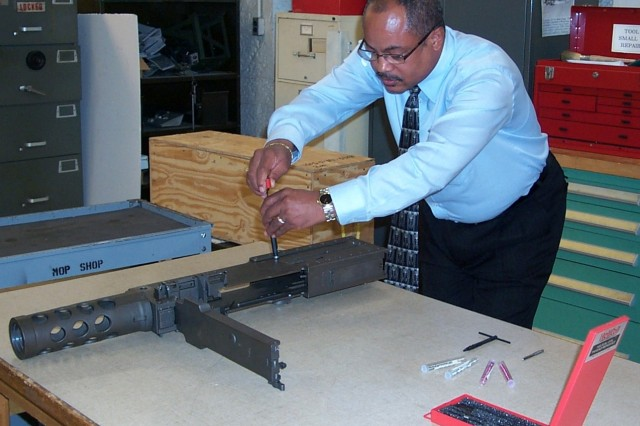 TACOM Life Cycle Management Command equipment specialist Walter Hilliard performs a new repair procedure that prevents M2 machine guns from becoming unserviceable.  The repair is slated to save $3.9 million over the next three years.