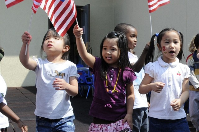 U.S. Army Garrison Daegu Child Development Center students march and wave American flags during the playing of the Army Song.