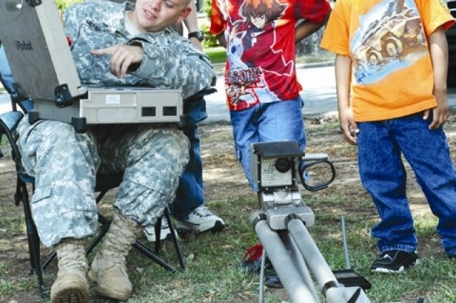 Spc. Kyle H. McFarland, team member with the 733rd Ordnance Company (Explosive Ordnance Detachment) at Fort Gillem, explains to a group of children participating in the 233rd Army Birthday activities held Tuesday at Fort McPherson, how the Pac Boc robot searches, identifies and renders safe explosive devices.