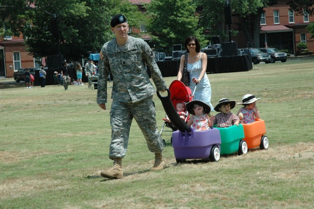 Lt.Col. Ken Hammond, chief, plans branch, operations division, U.S. Army Reserve Command, pulls his caravan of triplets, Sophia, Evan and Clare, 2, while his wife, Giovanna, pushes their youngest in a stroller. The family braved the rising temperatures to enjoy the birthday festivities.