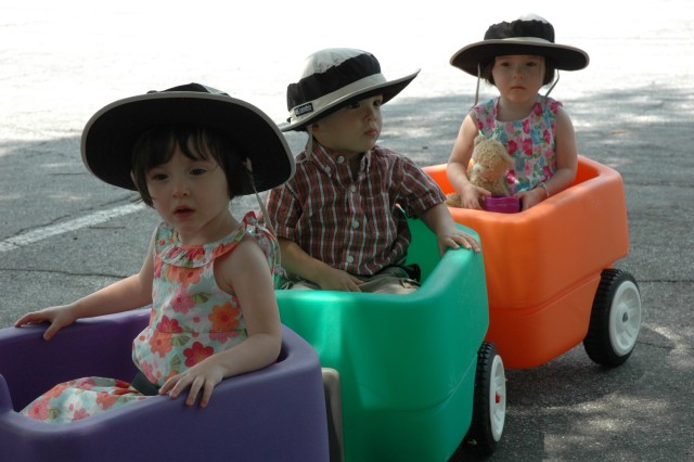 Sophia, Evan and Clare, 2, the Hammond Triplets, ride through the festival in style, pulled by their father Ken, chief, plans branch, operations division, U.S. Army Reserve Command. The three wore broad-brimmed hats to help brave the rising temperatures.
