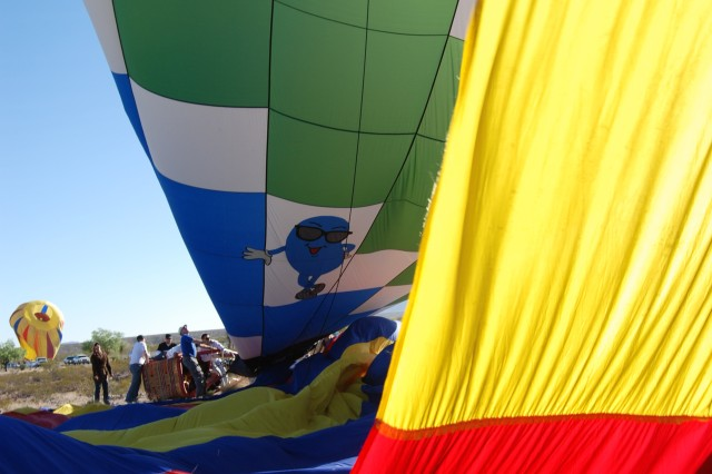 Chase crews hold down the basket and propane tanks while deflating the balloon, Cool Beans, during the 2008 International Balloonfest in Anthony, Texas.