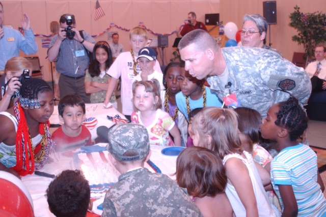 "Children help Col. Richard Piscal, Fort Riley garrison commander, blow out candles on a birthday cake celebrating the U.S. Army's 233rd birthday during a book reading party June 10 on post. The new book ""Happy Birthday, U.S. Army!"" is from Army Family and Morale, Welfare and Recreation Command's Child and Youth Services. Its 25 pages are kid-oriented, with plenty of pictures, graphics and history."
