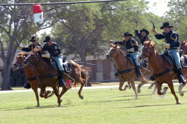 Mounted Soldiers from the 1st Cavalry Division's Horse Cavalry Detachment fire blanks into the air as they lead a cavalry charge across the 1st Cavalry Division parade field during a June 10 change of responsibility ceremony at Fort Hood, Texas.