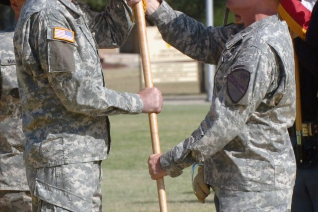 The outgoing 1st Cavalry Division command sergeant major, Command Sgt. Maj. Donald R. Felt (right), relinquishes responsibility for the division by passing the division guidon to Maj. Gen. Daniel P. Bolger, commanding general, 1st Cav. Div. during a change of responsibility ceremony June 10 at Fort Hood, Texas. Bolger in turn passed the guidon to the division's incoming command sergeant major, Command Sgt. Maj. Rory L. Malloy.