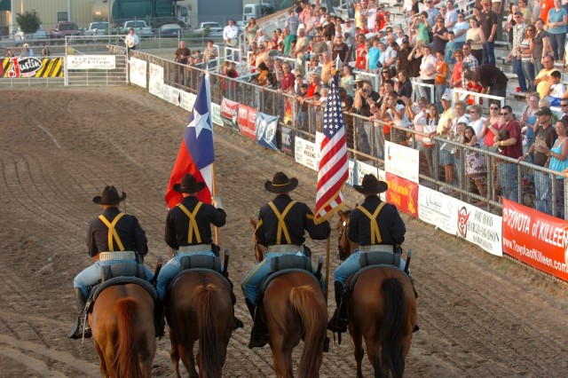 Prior to the start of a rodeo, a large crowd observes as a color guard made up of four mounted troopers from the 1st Cavalry Division's Horse Cavalry Detachment ride to the spot where they will post the national colors along with the Texas state flag during a ceremony at the Killeen rodeo grounds in Killeen, Texas June 6.
