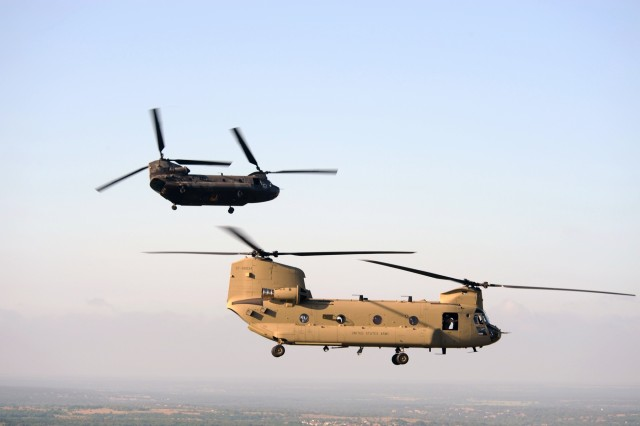 A CH-47D Chinook helicopter in the distance breaks away from formation with its replacement, the CH-47F, in its last flight out of Fort Hood, Texas, June 10. Both helicopters are assigned to Company B, 2nd Battalion, 227th Aviation Regiment, 1st Air Cavalry Brigade, 1st Cavalry Division.