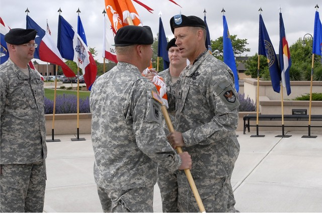 "Col. Timothy R. Coffin (right), commander of the 1st Space Brigade, passes the unit colors of the 53rd Signal Battalion (SATCON) to its new commander Lt. Col. Patrick L. Kerr (left) with outgoing commander Lt. Col. Scott M. Geiger (center) looking on during a change of command ceremony held on the morning of June 4 at the Medal of Honor Park on Peterson Air Force Base. Geiger has held the responsibilities of commander for the battalion for the past 24 months. The battalion provides critical, wideband satellite communications important in today's operational environment. Its motto is ""We Control The High Ground."""