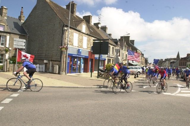Mike Buckley arrives in Les Pieux, France, during the second day of the Road to Liberty cycling tour, carrying the American flag while riding in the lead peloton. A native of Utah, Buckley is stationed in Stuttgart, Germany.