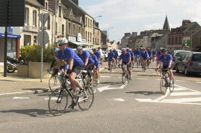 Staff Sgt. Kristopher Lindsey, an avid cyclist, leads several other riders around the corner of the town hall in Les Pieux, France, the first stop on second day of the three-day cycling tour honoring those Soldiers who battled for freedom, liberty and peace on D-Day.