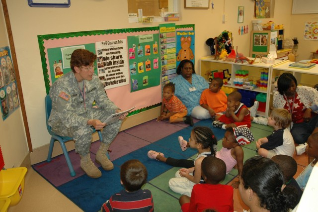 "As the pre-kindergarten students gather about her feet, Col. Marguerite Garrison, commander, U.S. Army Garrison, reads ""Happy Birthday, U.S. Army"" during the Army Birthday celebration held June 11 at the Child Development Center on Fort McPherson. The book is a special story about the Army\'s 233 year history."