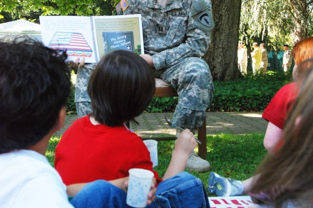 """Capt. Adam Schmidt, U.S. Army Europe executive service division, reads """"The Army Story"""" to children from the Patrick Henry and Mark Twain Village child development centers during Army Birthday Celebrations June 12. The celebration, which included the traditional cake, took place in the USAREUR headquarters garden and included Soldiers, Family members and civilian employees."""