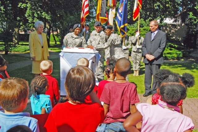 Civilian employees Ingrid Levene, left, and Norbert Hooks, right, along with 50 children from the Patrick Henry and Mark Twain Village child development centers watch (from left) Pvt. 1st Class Jasmine Carey, the youngest Soldiers assigned to U.S Army Europe headquarters, Col. Kirk Lawrence, USAREUR deputy chief of staff, and Chief Warrant Officer Eddie Lee Royal, the oldest Soldier assigned to USAREUR headquarters, cut a cake during celebration of the Army 233rd birthday June 12. The celebration took place in the USAREUR headquarters garden and included Soldiers, Family members and civilian employees.