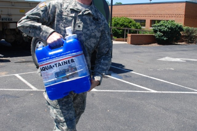Indiana Army National Guard Spc. Marcus McDowell carries a seven-gallon tank of water for a Hope, Ind. resident Wednesday, June 11, 2008. McDowell, a combat engineer with 113th Engineer Battalion headquarted in Gary, Ind., deployed to southern Indiana as part of Operation Noah's Ark.
