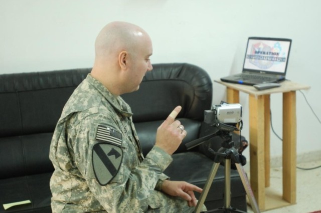 Chaplain (Capt.) Charles Leggett, a Richmond, Va., native, counts down to let a Soldier know when to begin reading his story May 27. Leggett is the chaplain for the 168th Brigade Support Battalion, 1st Sustainment Brigade, in support of Multi-National Division-Baghdad.