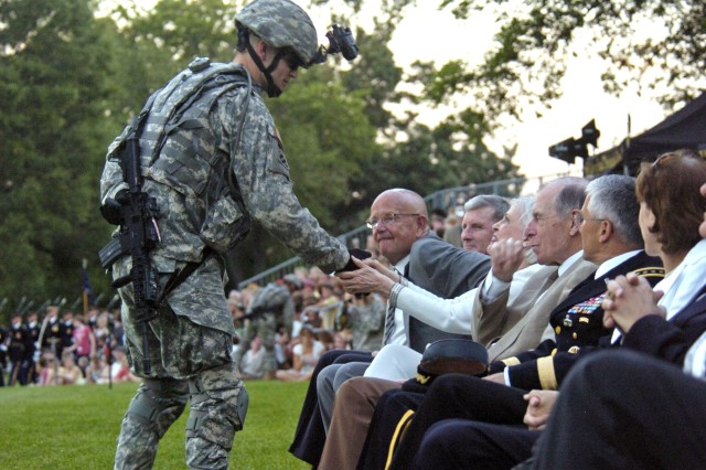 "Sgt. Jordan Ramsey, of Alpha Company, 4th Battalion, 3rd U.S. Infantry, shakes hands with Carol Meyer, wife of Gen. Edward C. Meyer (ret.), sitting to her left, next to Gen. George Casey Jr., Army chief of staff. Ramsey and other Soldiers of ""today's Army"" introduce themselves with prepared speeches during Twilight Tattoo performances and then fan out into the audience shaking hands."