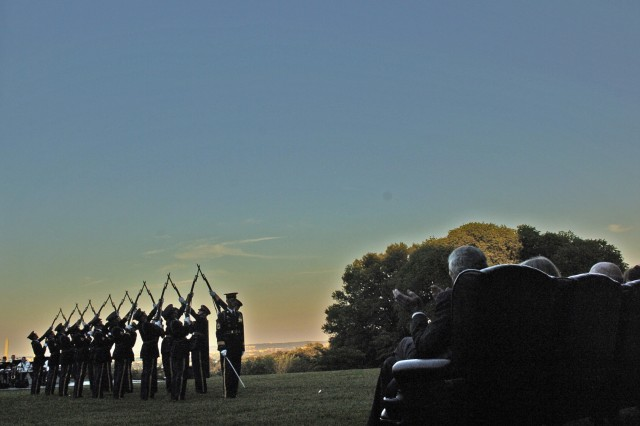 Drillmaster Sgt. 1st Class Devon McCann presents the Army Drill Team to a special Army birthday performance of Twilight Tattoo on Fort Myer's Whipple Field hosted by Army Chief of Staff Gen. George W. Casey Jr. Gen. Former Army Chief of Staff Gen. Dennis J. Reimer (ret.) applauds from his seat (right).