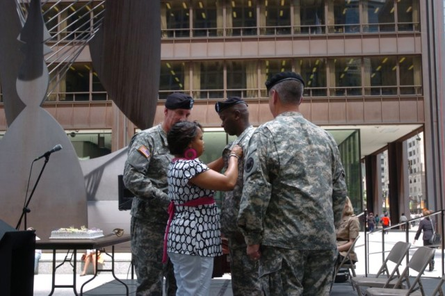 Staff Sgt. Terrence L. House receives the Combat Action Badge during the Army's 233rd birthday celebration at Daley Plaza, Chicago, June 11. Nichea House pins the Combat Action Badge on her husband while Maj. Gen. Peter S. Cooke looks on.