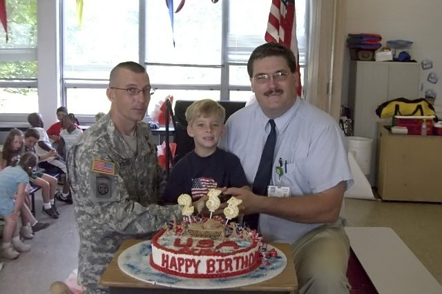 Sgt. 1st Class Jerry Whitaker poses for a photo with his son, Jacob, and Jody Kane, principal of William A. Walton Elementary School. Whitaker, stationed at Fort Pickett, Va., is a Virginia National Guardsman who volunteered to celebrate the Army's Birthday with ihs son's kindergarten class.