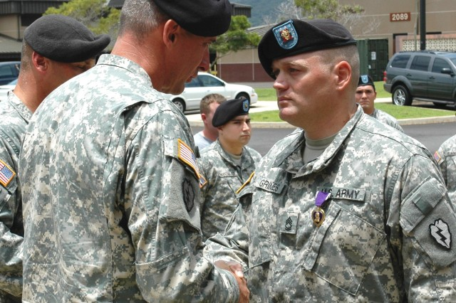 """Schofield Barracks, Hawaii - Brig. Gen. Robert B. Brown, deputy commanding general, 1st Battalion, 14th Infantry Regiment """"Golden Dragons,"""" 2nd Stryker Brigade Combat Team, commends Sgt. 1st Class Willie S. Grimes, tanker, 1-14th 2nd SBCT, after presenting him with a Purple Heart at a ceremony in front of 1-14th Battalion Headquarters, Schofield Barracks, June 6. Grimes received the award for wounds he sustained from an improvised explosive device while serving as a sniper during a mission in Sadr City, Iraq, last April."""