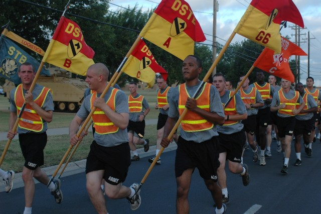 Soldiers from the 1st Cavalry Division's Special Troops Brigade, carrying their company guideons, run past the division headquarters 12 June on Fort Hood, Texas. The early morning workout began the 'First Team's' celebration of the Army's 233rd birthday.