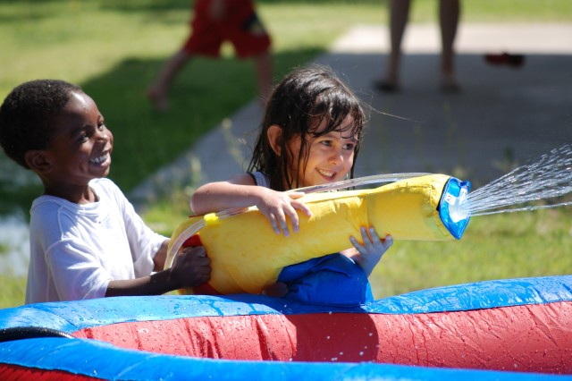 """Children laugh as they soak their friends coming down the water slide during a Child and Youth Services picnic."""""""