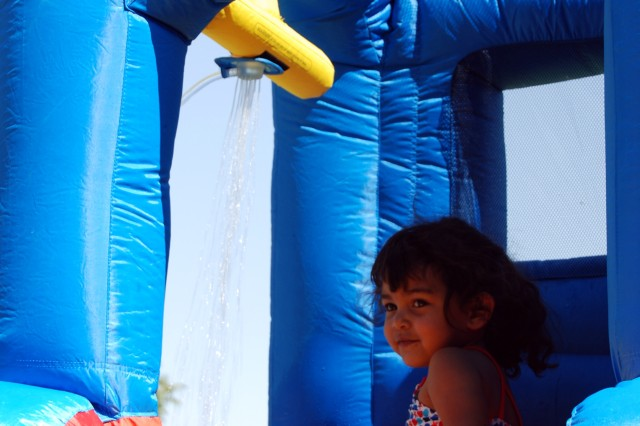 A child looks to her teacher for encouragement before going down the waterslide during a child and Youth Services picnic on Fort Bliss.""