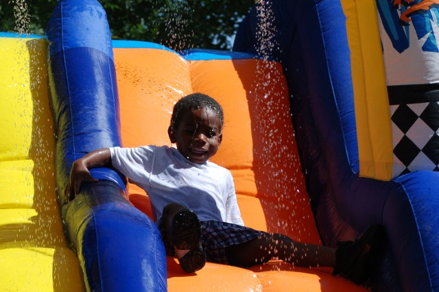 """A child laughs his way down a waterslide at a picnic sponsored by Fort Bliss Child and Youth Services. """""""