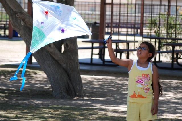 A School Age Services child enjoys the afternoon spent in the park flying kites in honor of the Army's 233rd Birthday.