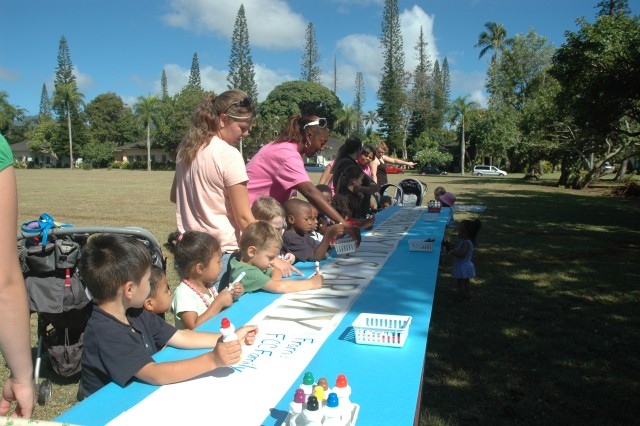 SCHOFIELD BARRACKS, Hawaii - Family members and their child care providers line up to sign a birthday banner, June 10, at Canby Field, Schofield Barracks. The banner, which was decorated with family photos, will be laminated and hung outside the Family Child Care office.
