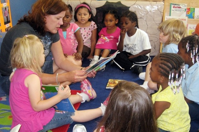 """Carol Rosenberg, wife of Lt. Col. Gary Rosenberg, commander of U.S. Army Garrison Bamberg, Germany, reads the """"Happy Birthday Army"""" book to children at Bamberg's Child Development Center June 9 in celebration of the Army's 233rd"""