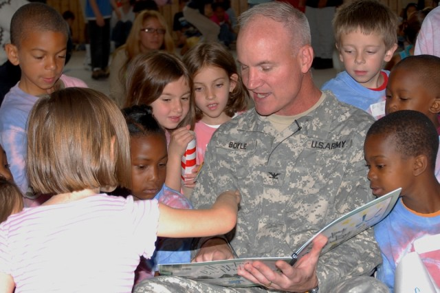 Col. Brian Boyle, commander of U.S. Army Garrison Grafenwoehr, takes time to engage in a question and answer session on the Army Birthday story he'd just read to 200 children at the Vilseck School Age Services facility in Germany.
