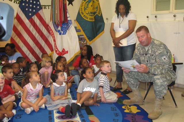 "Sgt. Maj. of the Army Kenneth O. Preston reads the Army Birthday Children's Storybook Thursday to about 20 children at Walter Reed Army Medical Center's Child Development Center at Forest Glenn, located in Silver Spring, Md. After the reading, Preston and two of the children blew out candles on the official ""Army birthday"" cake followed by the singing of the Army Song. The Army Birthday Children's Storybook was written for children by Army Family Morale, Welfare and Recreation Command to help Army children understand the importance, history, contributions and sacrifices their parents make."
